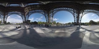 360 VR View from underneath the Eiffel Tower in Paris, France. 360 photo - Under the Eiffel Tower. People walking and relaxing on ground with mural Endless Sleep royalty free stock photography