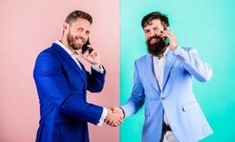 Vraagpartner Bezig met gesprek bevestig regelingen De zakenlieden gebruiken online moderne gadgetsmartphone met stock foto