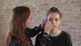 Vraagt de professionele de make-upkunstenaar van de close-upvrouw was op gezicht van jong leuk meisje plastic make-up voor biosko stock video