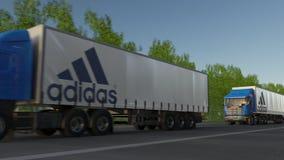 Vracht semi vrachtwagens met Adidas-inschrijving en embleem het drijven langs bosweg Het redactie 3D teruggeven Stock Fotografie
