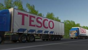 Vracht semi vrachtwagens met Tesco-embleem het drijven langs bosweg Het redactie 3D teruggeven Royalty-vrije Stock Fotografie