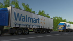 Vracht semi vrachtwagens met Walmart-embleem het drijven langs bosweg Het redactie 3D teruggeven Stock Fotografie