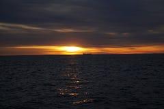 Vrachtboot op de horizon bij zonsopgang stock afbeelding