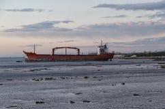 Vrachtschip aan de grond van de kust stock fotografie