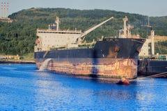 Vrachtschip bij pijler weinig het Noordenhaven stock foto's