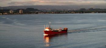 Vrachtschip dat in haven aankomt stock afbeelding