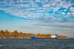 Vrachtschip die op de rivier aan de haven varen stock foto