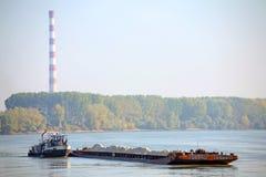 Vrachtschip en het verwarmen installatie in de Donau Stock Afbeeldingen