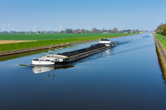 Vrachtschip met steenkool op het kanaal in Wesermarsch wordt geladen die Stock Foto's