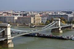 Vrachtschipschip met auto's onder de kettingsbrug in Boedapest stock afbeelding