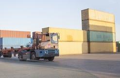 Vrachtwagen die in haven dragende containers werken Stock Afbeeldingen