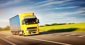 Vrachtwagen die zich op zonnige avond bewegen stock foto's
