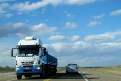 Vrachtwagen en auto op een lange weg aan de hemelhorizon Stock Foto