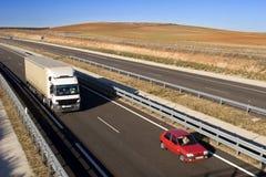 Vrachtwagen en auto op weg Stock Fotografie