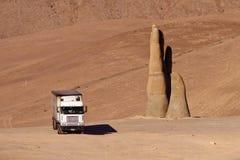 Vrachtwagen en een handbeeldhouwwerk in de woestijn Stock Foto's