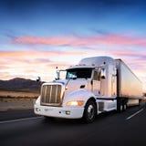 Vrachtwagen en weg bij zonsondergang - vervoersachtergrond Royalty-vrije Stock Foto's