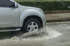 Vrachtwagen het drijven door vloedwater op de weg royalty-vrije stock foto's
