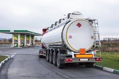 Vrachtwagen met de brandstof van de benzinetank alvorens bij een benzinestation leeg te maken stock foto