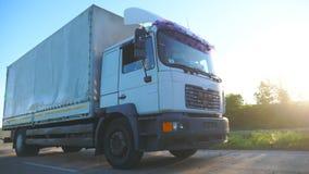 Vrachtwagen met ladingsaanhangwagen die op weg berijden en goederen vervoeren in zonsondergangtijd Vrachtwagen het berijden door  stock videobeelden