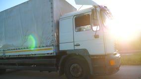 Vrachtwagen met ladingsaanhangwagen die op weg berijdt en goederen vervoert in zonsondergangtijd Vrachtwagen het berijden door la stock video