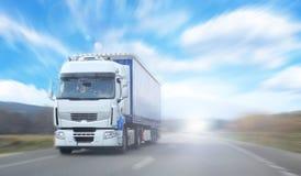 Vrachtwagen op onscherpe weg over blauwe bewolkte hemelbackgrou