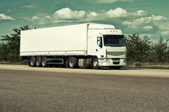 Vrachtwagen op weg, blauwe hemel, het concept van het ladingsvervoer, gestemd geel Stock Afbeelding