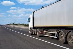 Vrachtwagen op weg met container en bewolkte hemel, het concept van het ladingsvervoer Royalty-vrije Stock Foto