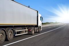 Vrachtwagen op weg met container en heldere zon, het concept van het ladingsvervoer Stock Foto