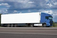 Vrachtwagen op weg met witte lege container, blauwe hemel, het concept van het ladingsvervoer Stock Foto's