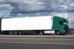 Vrachtwagen op weg met witte lege container, blauwe hemel, het concept van het ladingsvervoer Royalty-vrije Stock Foto's
