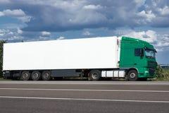 Vrachtwagen op weg met witte lege container, blauwe hemel, het concept van het ladingsvervoer Royalty-vrije Stock Afbeelding