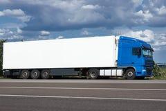 Vrachtwagen op weg met witte lege container, blauwe hemel, het concept van het ladingsvervoer Stock Fotografie