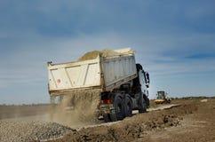 Vrachtwagen tippend grint stock afbeeldingen
