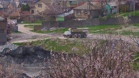 Vrachtwagenritten op de stoffige weg in de fabriek achter bloeiende bomen stock video