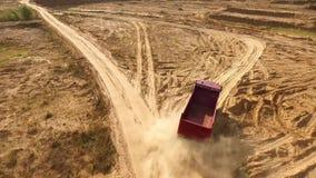 Vrachtwagenritten op de weg van de zandsteengroeve scène Hoogste mening van stortplaatsvrachtwagen het drijven bij de gele landwe stock video