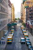 Vrachtwagens 'Penske 'op een rij in de smalle straat van NYC met mensen die langs lopen royalty-vrije stock afbeeldingen