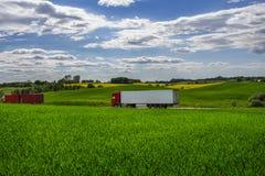 Vrachtwagens die goederen op de asfaltweg vervoeren tussen groene gebieden in een landelijk landschap onder een bewolkte blauwe h Stock Foto