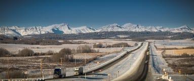 Vrachtwagens die op lange afstand in bergen op weg in de winter drijven Stock Afbeeldingen