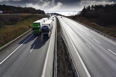 Vrachtwagens die op toneelweg bij zonsondergang afleiden Stock Afbeeldingen