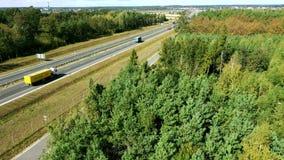 Vrachtwagens en auto's het drijven door weg tussen bos stock video