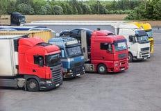 vrachtwagens in het Parkeerterrein dichtbij de weg stock foto