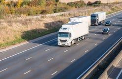 Vrachtwagens op de autosnelweg stock foto's
