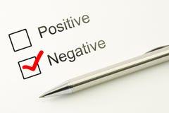 Vragenlijst: negatieve keus of positieve, duidelijke checkbox met een pen op document achtergrond Afkeuringsconcept Stock Foto's