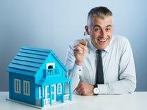 Vrai agent immobilier avec la maison modèle photographie stock