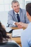 Vrai agent immobilier de sourire serrant la main à son nouvel acheteur Photos stock