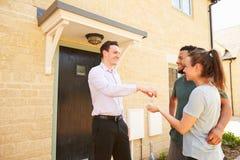 Vrai agent immobilier donnant des clés de maison à de nouveaux propriétaires images libres de droits