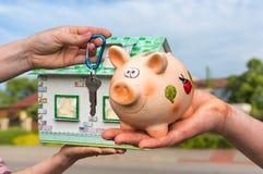 Vrai agent immobilier donnant la maison de clé de maison et modèle à un nouveau pro Image stock