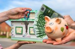 Vrai agent immobilier donnant la maison de clé et de modèle de maison à un nouvel appui vertical Image libre de droits