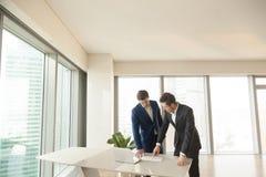 Vrai agent immobilier expliquant le plan de pièce au client Photos stock