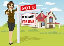 Vrai agent immobilier femelle se tenant à côté de vendre pour le signe de vente devant le cottage classique Photos stock